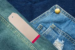 Rip jeans texture background with tag. Rip denim jeans background with seam of jeans fashion design and tag Stock Images