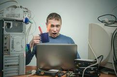 Riparatore che lavora al computer portatile Immagine Stock