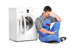 Riparatore che propone vicino ad una lavatrice fotografia stock