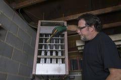 Riparatore Cleaning The Grates di una fornace di gas Immagini Stock