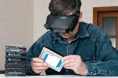 In riparatore esperto del computer con una lente sulla sua testa è drive del hard disk diagnostico in officina fotografia stock