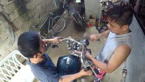 Riparatori della bici del motore che martellano la maniglia del metallo archivi video