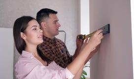 Riparazione in casa, giovane coppia con la misura di nastro in mani che appendono scaffale sulla parete durante il rinnovamento i stock footage