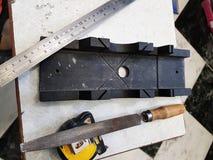 Riparazione - costruzione con gli strumenti, misura di nastro, contenitore di mitra, archivio, seghetto a mano per metalli, righe immagini stock