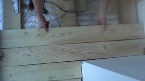 Riparazione, costruzione, pavimento e concetto della gente - vicino su dell'uomo che installa pavimentazione di legno archivi video