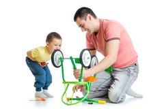 Riparazione del figlio e del padre che ripara la ruota di bicicletta Immagini Stock Libere da Diritti