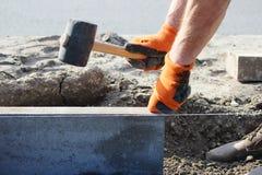 Riparazione del marciapiede I muratori lavoranti professionisti in camici trasmettono i bordi a porre le lastre per pavimentazion fotografia stock libera da diritti