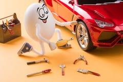 Riparazione del meccanico dell'uovo la ruota di automobile Immagini Stock Libere da Diritti
