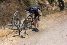 Riparazione del mountain bike nel parco della regione selvaggia del ranch del merlano fotografia stock