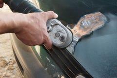 Riparazione del riparatore del lavoratore del meccanico insabbiando la carrozzeria di lucidatura e preparando per la verniciatura fotografia stock