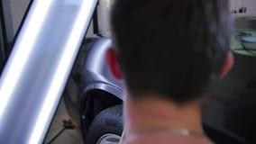 Riparazione dell'ammaccatura di Paintless Il giovane padrone allinea l'ammaccatura sulla macchina con lavora all'uncinetto lo str video d archivio