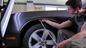 Riparazione dell'ammaccatura di Paintless Il padrone allinea il gancio dell'ammaccatura sull'automobile senza pittura nell'offici stock footage