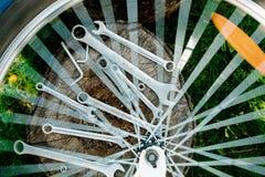 Riparazione della bicicletta Strumenti, strumento per la riparazione della bici sui precedenti di legno del ceppo con i raggi di  Immagine Stock