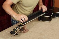 Riparazione della chitarra e servizio - cerchi neri del collo della chitarra di frantumazioni del lavoratore fotografie stock
