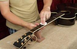 Riparazione della chitarra e servizio - inumidimento del lavoratore ed impregnazione di un olio speciale della chitarra del nero  fotografia stock libera da diritti