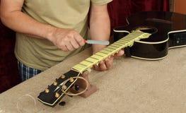 Riparazione della chitarra e servizio - lavoratore affilare chitarra del nero del dado del ponte dell'utensile speciale la servo fotografia stock
