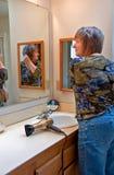 Riparazione della donna i suoi capelli in specchio della stanza da bagno Immagini Stock