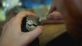 Riparazione delle gemme in un anello con uno strumento per il processo dell'intarsio video d archivio