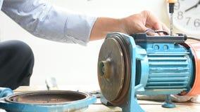 Riparazione di attrezzatura di lavoro dell'uomo e del motore elettrico sul fondo di legno del pavimento Meccanico o attrezzatura  stock footage