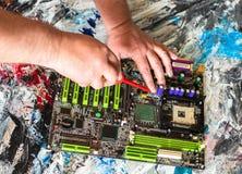 Riparazione di una scheda madre del PC con un cacciavite con una maniglia rossa immagine stock libera da diritti