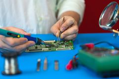 Riparazione di video bordo di convertitore del segnale della TV Saldatura dei componenti elettronici da un ingegnere delle TV mod immagini stock