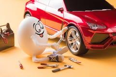 Riparazione divertente del meccanico di automobile dell'uovo la ruota Immagine Stock Libera da Diritti