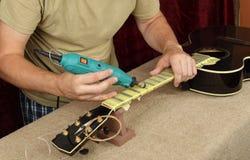 Riparazione e servizio della chitarra - dremel dei cerchi del collo della chitarra acustica del lavoratore e pasta di lucidatura  immagine stock libera da diritti
