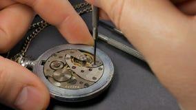 Riparazione meccanica dell'orologio L'orologiaio monta un orologio stock footage