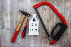 Riparazione nel concetto della casa Gli strumenti della costruzione e la casa bianca modellano su fondo di legno fotografia stock libera da diritti