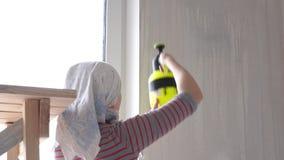 Riparazione nell'appartamento - una giovane donna dell'aspetto europeo fa le riparazioni a casa - innesco della parete archivi video