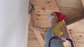 Riparazione nell'appartamento - una giovane donna dell'aspetto europeo fa le riparazioni a casa - lucidatura di superficie della  video d archivio