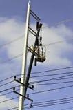 Riparazioni elettriche dagli elettricisti su un palo di potenza Fotografia Stock