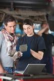 Riparazioni femminili di Explaing del meccanico al cliente Fotografie Stock Libere da Diritti