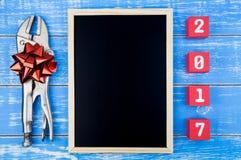 Ripari gli strumenti, il numero del buon anno e della lavagna 2017 sulla p rossa Fotografia Stock Libera da Diritti