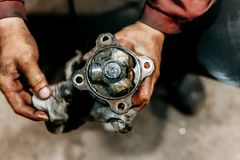 Ripari il giunto di costante-velocità in mani in garage, meccanico fotografie stock