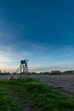 Riparo di legno di caccia accanto al campo marrone durante il tramonto Immagini Stock