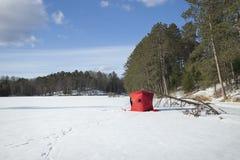Riparo rosso della pesca sul ghiaccio su un lago a distanza minnesota Immagine Stock