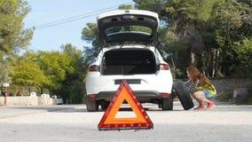 Ripartizione dell'automobile Gomma cambiante della donna su una strada archivi video