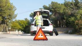 Ripartizione dell'automobile Gomma cambiante della donna su una strada video d archivio