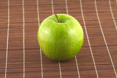 Ripe apple on brown wicker straw mat close up Stock Photo