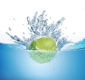 Ripe apple falling into water. Royalty Free Stock Photo