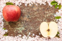 Ripe apple in frame of blossom petals stock photography