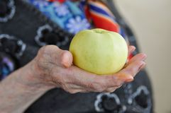Ripe Apple in the hand of an elderly woman in a knitted vest for a walk. 90 years. Health and nutrition. Close-up royalty free stock photo