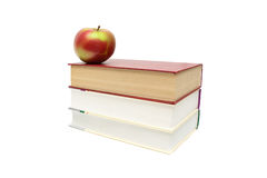 Ripe apple lies on a pile of books on a white background Stock Images