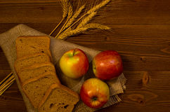 Ripe apple, square pieces of bread and ears on sacking on a wooden table Royalty Free Stock Photos