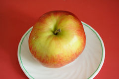 Ripe apple on the white plate Royalty Free Stock Images