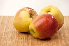 Ripe apples. Three ripe apples on wooden surface with light background Royalty Free Stock Photo