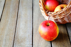 Ripe apples and a basket on wooden background royalty free stock photos