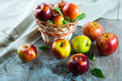 Ripe apples in the basket on the wooden table Royalty Free Stock Images