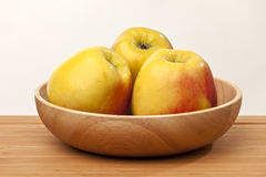 Ripe apples in bowl. Three white whole apples in wooden bowl with light background Royalty Free Stock Photography